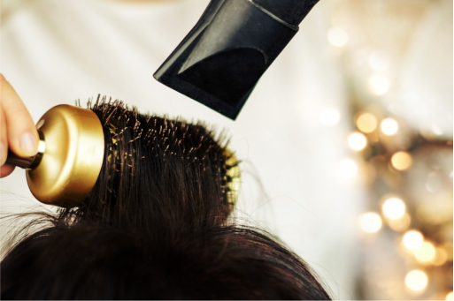 Close view of blow drying hair with a gold brush